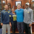 Coach Jim Harbaugh and recruit Jeremiah Holloman with University of Michigan football gift picture book WOLVERINE: A Photographic History of Michigan Football, Vol. 1